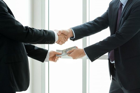 38923561 - businessmen making handshake while passing money, dealing & bribery concepts - soft focus