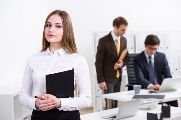 54634096 - young businesswoman with notebook standing at table, two businessman talking at background. concept of work.
