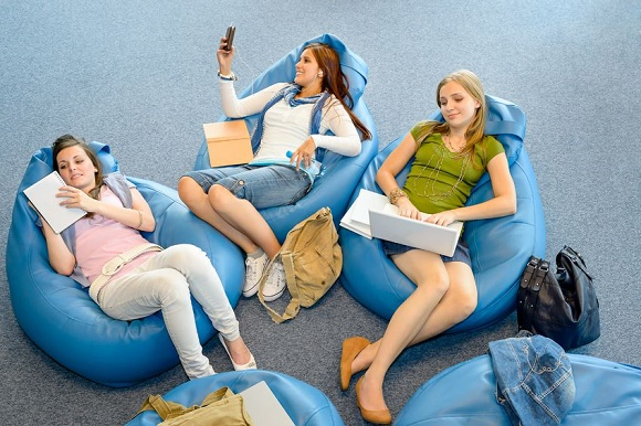 14048958 - young student girls resting on blue beanbags at library