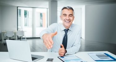 43397086 - smiling confident businessman giving an handshake, agreement and recruitment concept