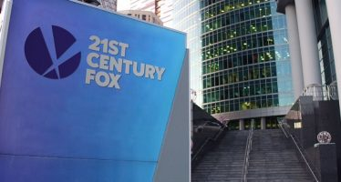66238481 - street signage board with 21st century fox logo. modern office center skyscraper and stairs background. editorial 3d rendering united states
