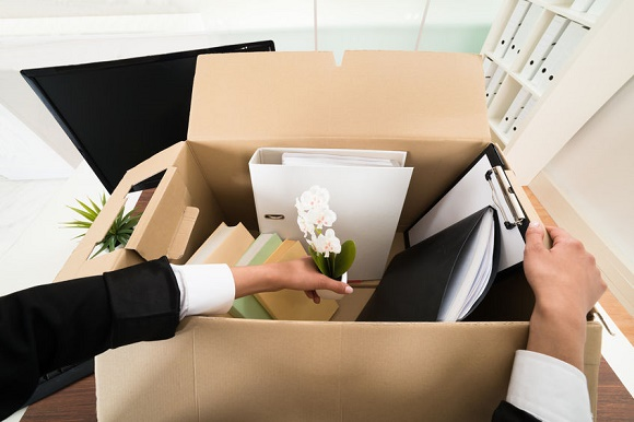 39731231 - high angle view of businesswoman packing personal belonging in box
