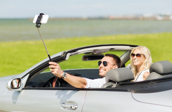 57276162 - road trip, leisure, couple, technology and people concept - happy man and woman driving in cabriolet car and taking picture with smartphone on selfie stick