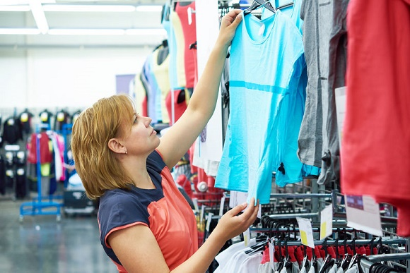 58310851 - woman chooses sportwear for fitness in the sports shop
