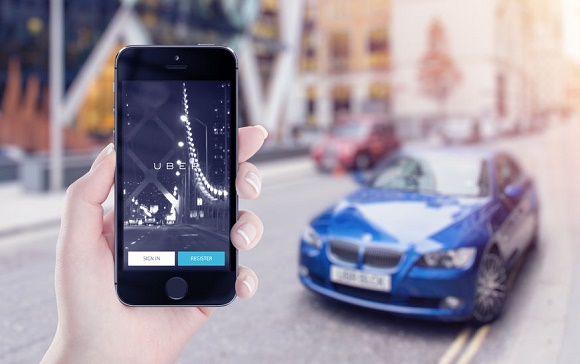 43260446 - varna, bulgaria - may 25, 2015: uber application startup page on the apple iphone 5s display in female hand. blurred street view with car and flare sun light on the background.