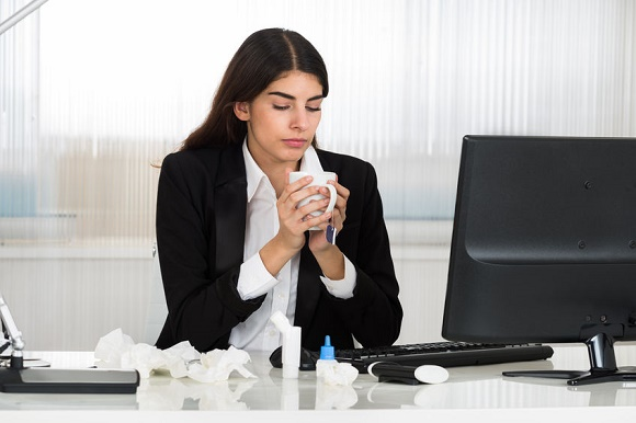 51726057 - sick young businesswoman holding cap of tee at computer desk in office