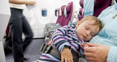 18766839 - flying with children  mother and sleeping two year old baby girl travel on a commercial airliner
