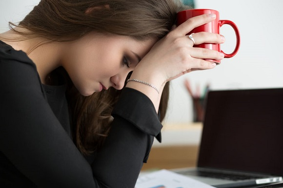 60029252 - tired female employee at workplace in office holding red cup and touching her head. sleepy worker early in the morning. overworking, making mistake, stress, termination or depression concept
