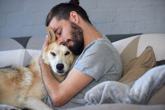 54381065 - hipster man snuggling and hugging his dog, close friendship loving bond between owner and pet husky