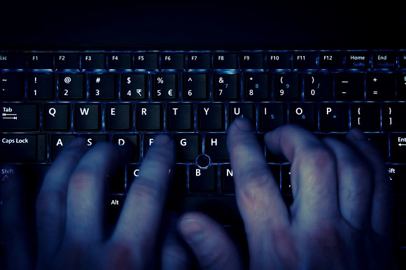 43182800 - hands typing on keyboard in blue light with motion blur