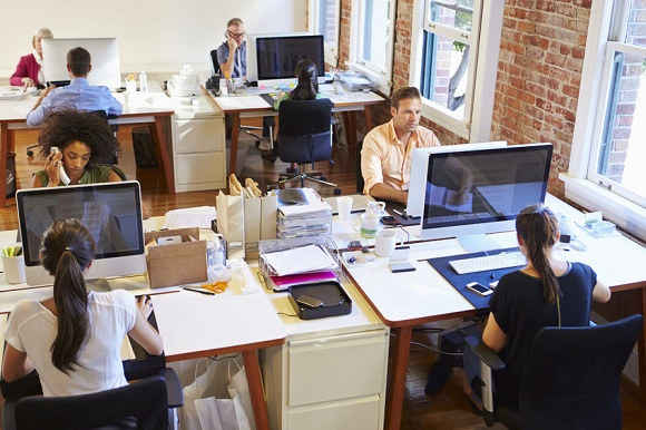 42307744 - wide angle view of busy design office with workers at desks