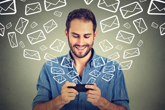46737877 - portrait young happy man busy sending messages emails from smart phone email icons coming out flying of mobile phone isolated on gray wall background. telecommunications, internet, data plan concept