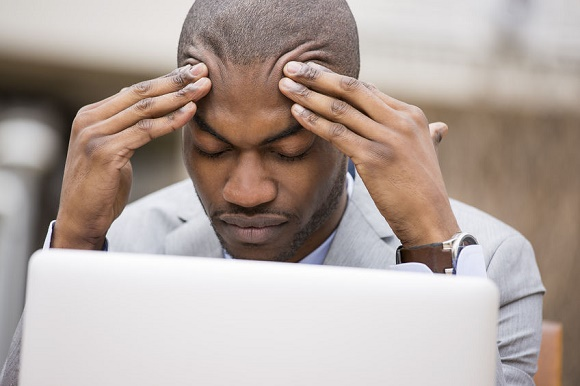 42175131 - stressed young businessman sitting outside corporate office working on laptop computer holding head with hands looking down. negative human emotion facial expression feelings.