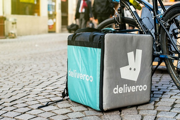 76287359 - strasbourg, france - apr 3, 2017: detail of deliveroo bike and cargo box parked in city with cafe terrace restaurant in the bakground to deliver on time the food to the client. deliveroo is a british online food delivery company with operations spread acr