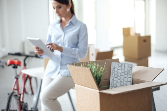 50939241 - business woman moving in a new office, she is using a digital tablet, selective focus, open cardboard box on foreground