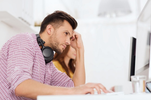 61743341 - deadline, startup, education, technology and people concept - sad stressed software developer or student with headphones and computer at office