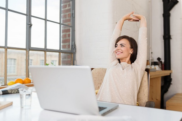32998519 - happy relaxed young woman sitting in her kitchen with a laptop in front of her stretching her arms above her head and looking out of the window with a smile