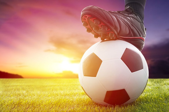 26273938 - football or soccer ball at the kickoff of a game with sunset