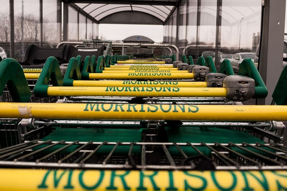 73979413 - a row of morrisons trolleys in an outdoor trolley bay.