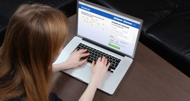33361162 - london, united kingdom - september 24, 2014: facebook homepage on computer screen teenage girl typing on laptop keyboard logging onto famous social network facebook home page and signing up