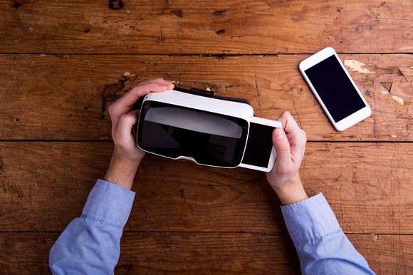 54232909 - hands of man holding virtual reality goggles and smart phone. flat lay. studio shot on wooden background.