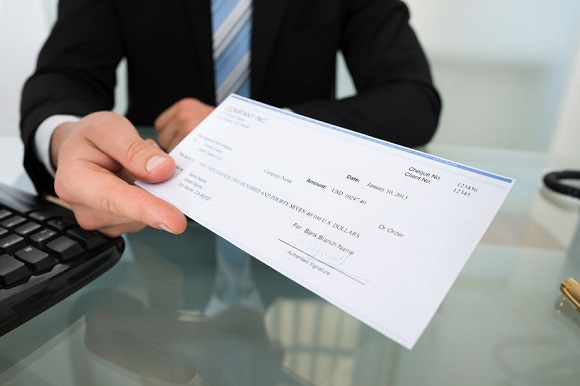 34263887 - midsection of businessman giving cheque at desk in office