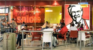35437986 - johannesburg, south africa - november 28, 2014: melting pot people at kfc restaurant in tambo international airport. kentucky fried chicken is a world famous fast food restaurant chain