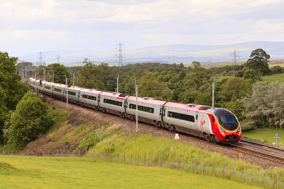 79363873 - virgin pendolino.  a virgin pendolino heads north through hackthorpe, cumbria.  virgin trains have operated the uk west coast main line rail franchise since 1987.