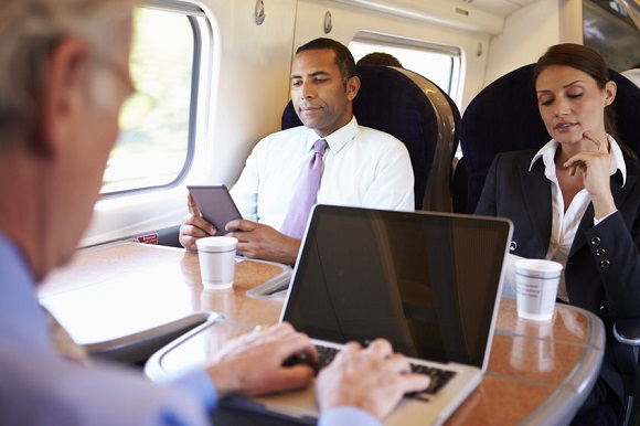 28159410 - businessman commuting to work on train and using laptop