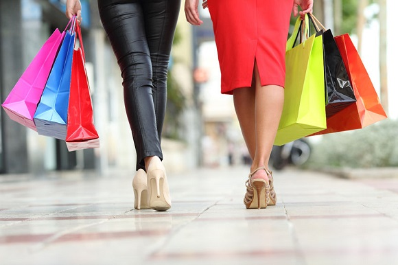 44973811 - two fashion women legs walking with colorful shopping bags in the street of a city