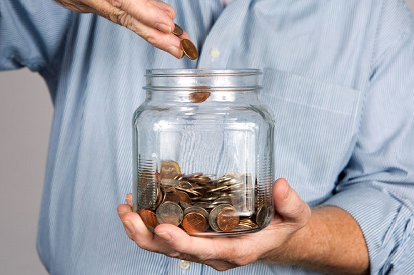 35999644 - man drops money into a glass jar for a savings account.