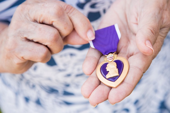 80426664 - senior woman holding the military purple heart medal in her hands.