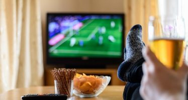 39302351 - television, tv watching (football match) with feet on table and huge amounts of snacks - stock photo