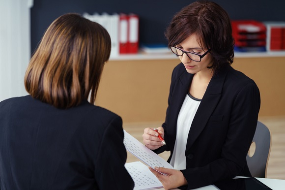 48654476 - two professional businesswomen in black suits having a one-on-one business meeting inside the office.