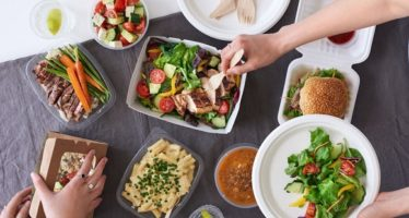 68221382 - convenient takeaway takeout food for party, overhead spread of assorted food with hands serving up